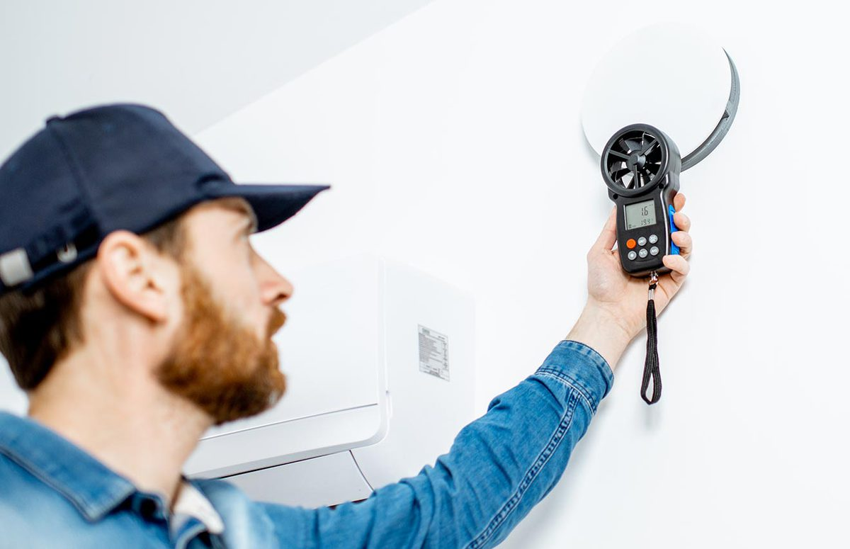 Person holding a device near a CO2 alarm