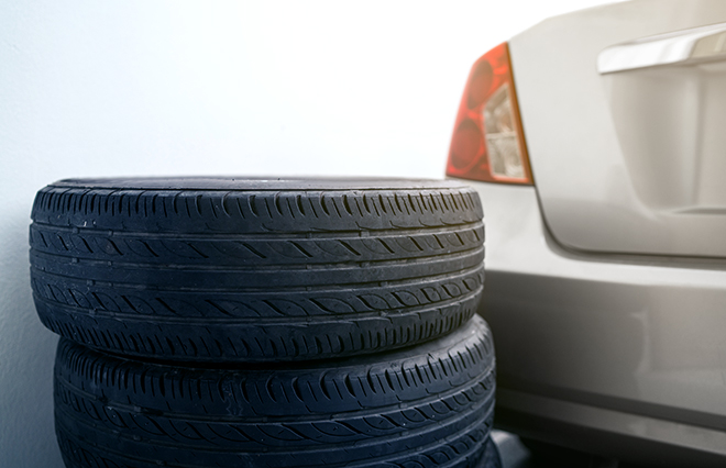 All season tires stacked neatly against the trunk of an Onlia insured vehicle in a clean garage