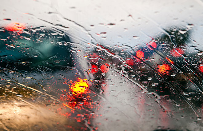 View of car tail lights through a rainy windshield
