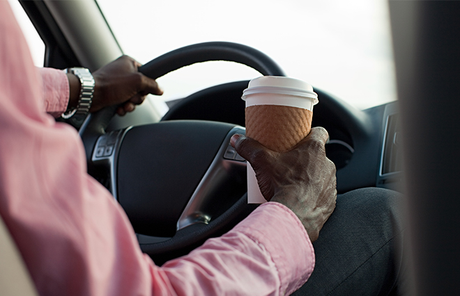 Person driving with one hand on the wheel and a coffee in the other hand