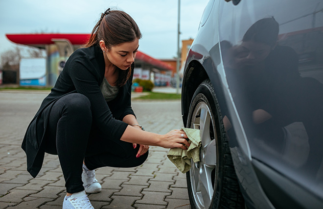 Woman cleaning her car hubcaps