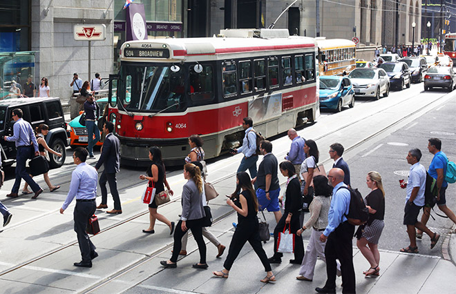 Pedestrians crossing a busy street in Toronto with a streetcar behind them