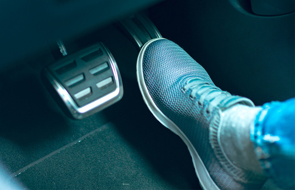 A person's foot stepping on a car brake pedal.