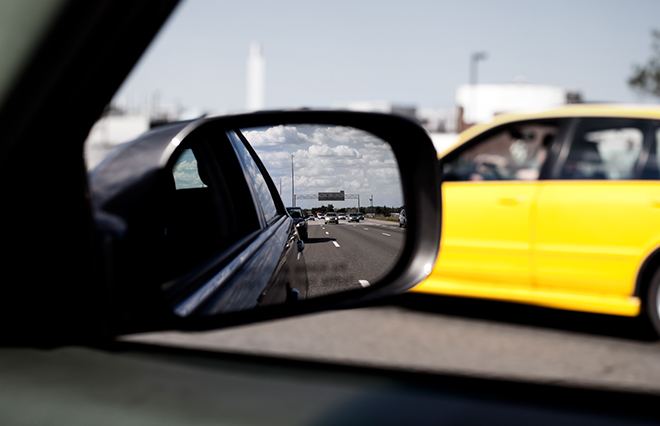 Image of a car in the side view mirror of an vehicle with Onlia insurance coverage