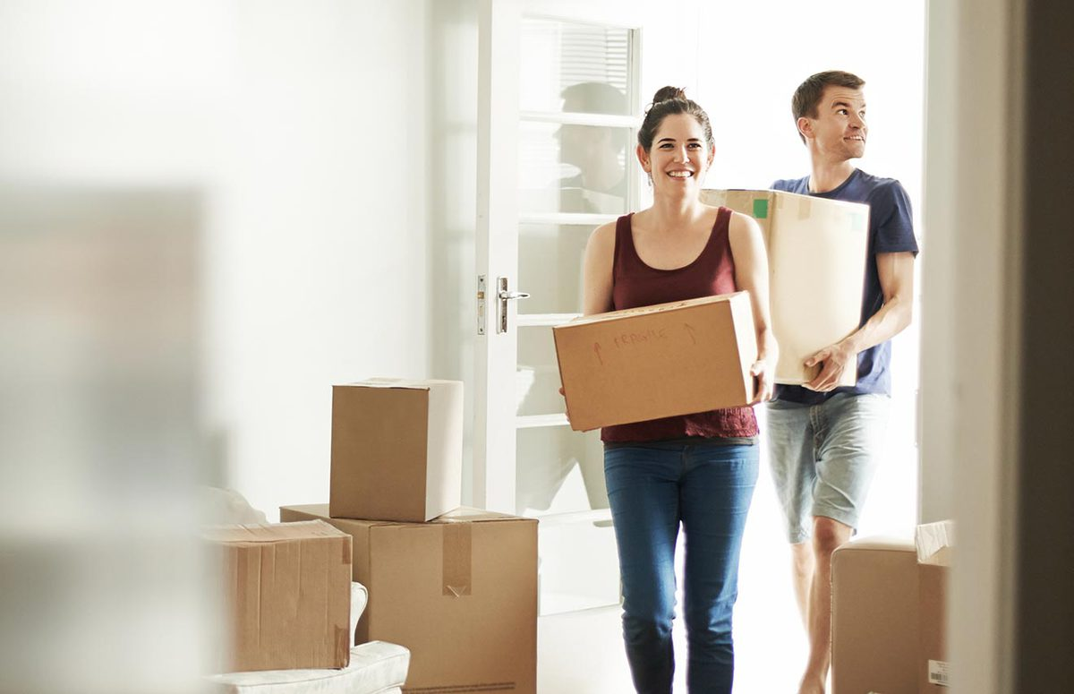 People carrying moving boxes into a home