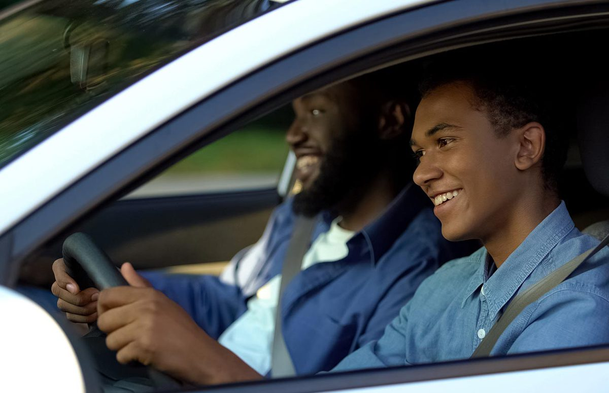 Teen driving a car with parent in the front seat
