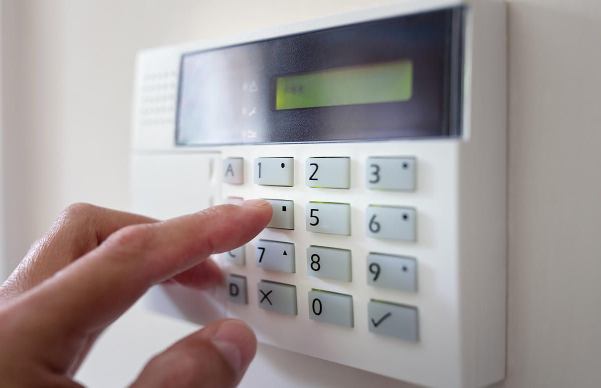 Person pushing buttons on a home alarm system